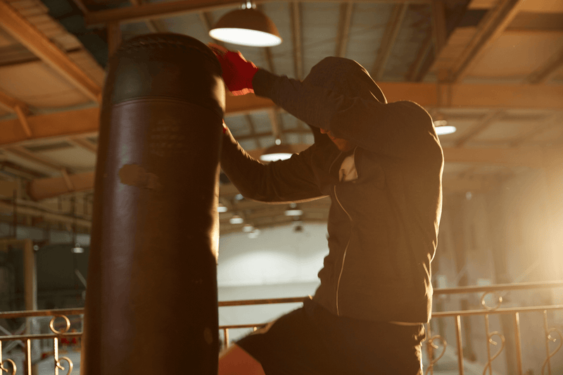 Hooded Man striking a Punching Bag with knee