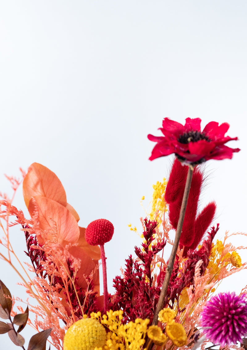 Autumn colors filled of bold yellow, oranges, pinks and reds floral decoration of preserved flowers