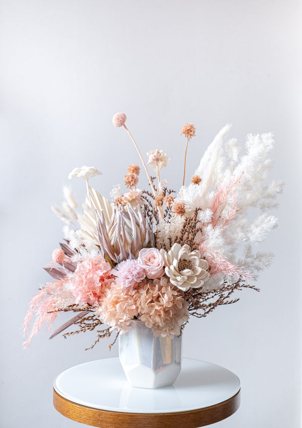 Peach white brown preserved flowers and dried protea along with imported sola flowers designed in an iridescent vase by singapore florist