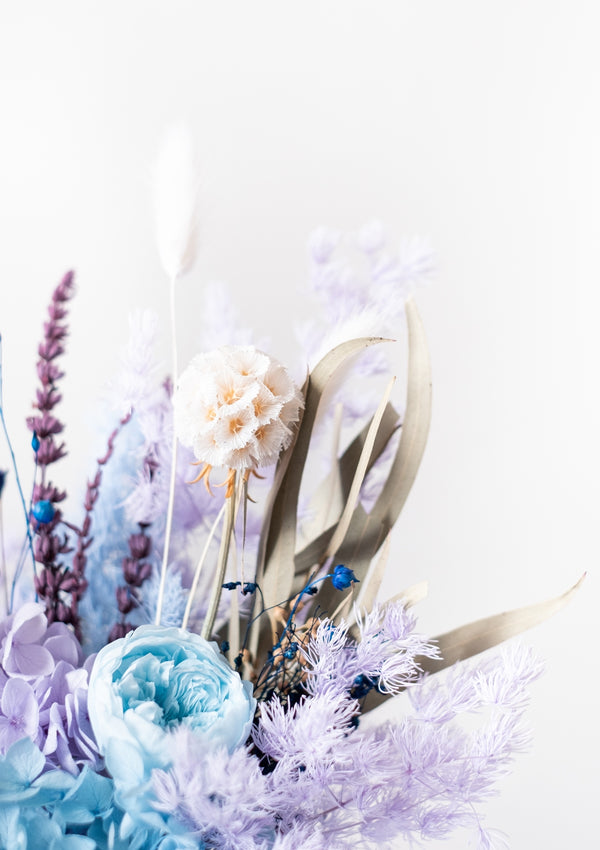 Cool blue, skyblue, pastel blues, cobalt blues filled preserved flower arrangement delicately curated in a ceramic white vase by florist in singapore
