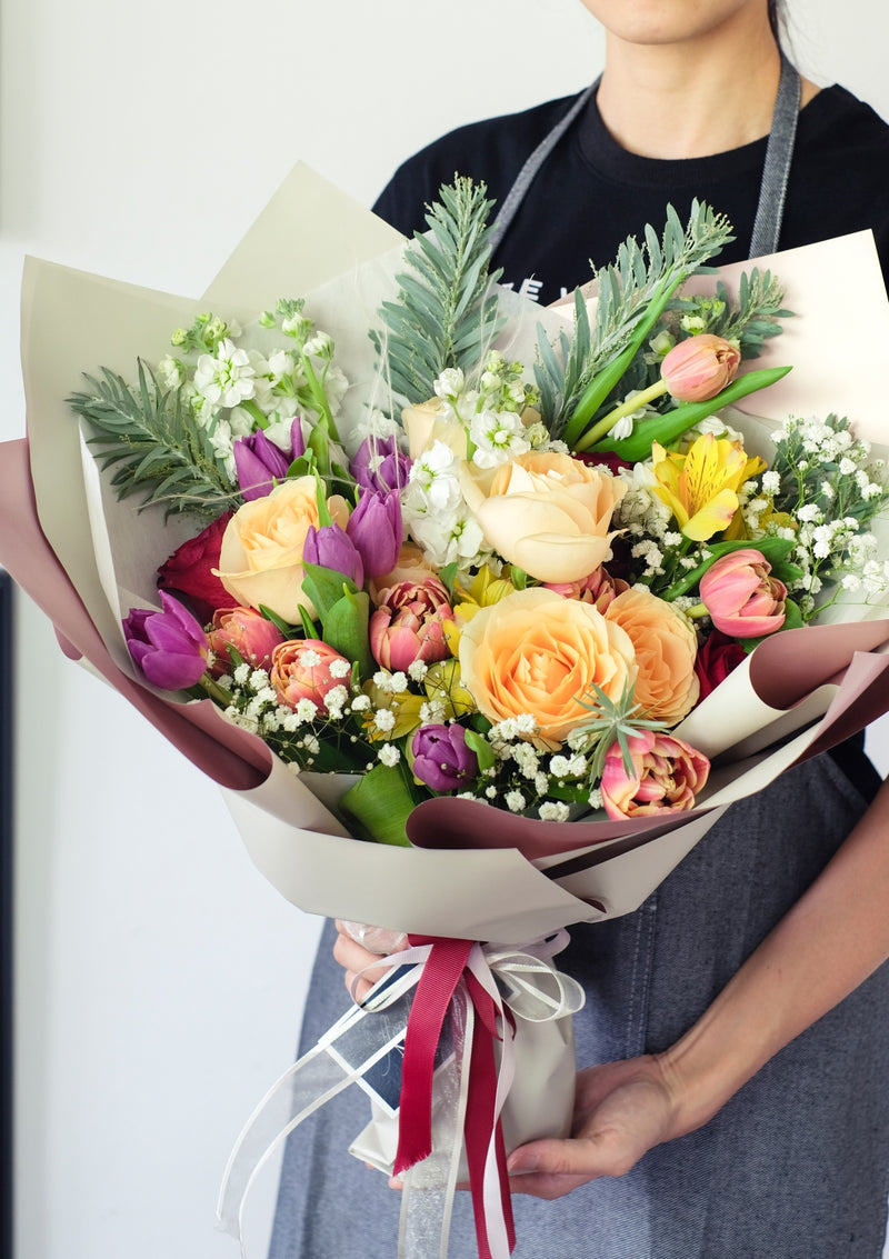 Cheerful peach roses amongst tulips and other fresh flowers with floral design curated by singapore top fresh flower florist floral mikelle