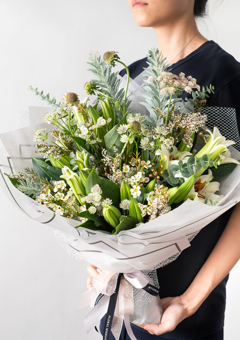 Opulent bouquet of fresh white lilies amongst a mix selection of premium filler flowers and wondrous greens finished in a classy wrapping