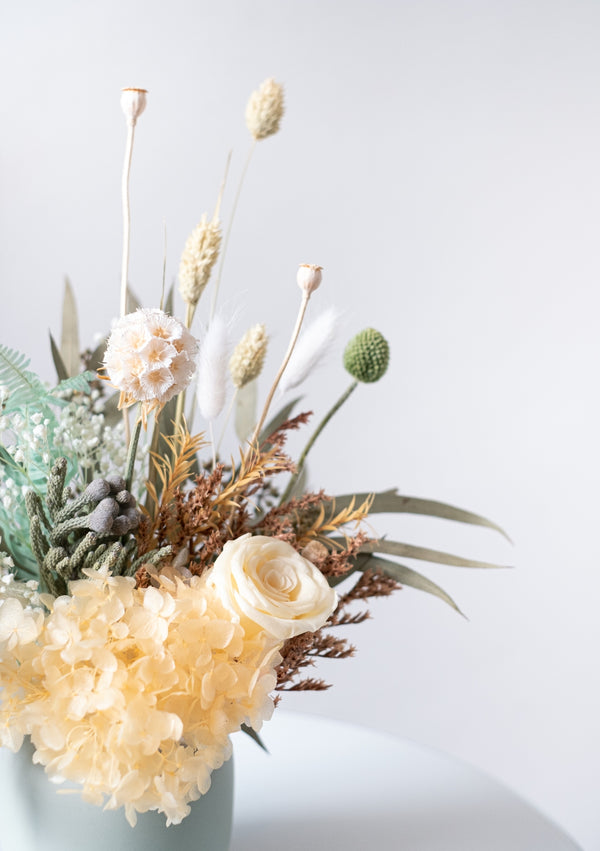 Greens and pastel yellow filled preserved flower arrangement with free delivery in singapore!