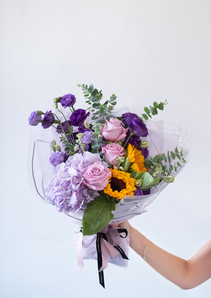 Lilac roses and hydrangea with yellow sunflowers created in a handtied bouquet by top singapore preserved flower florist specialising in customised flower arrangements