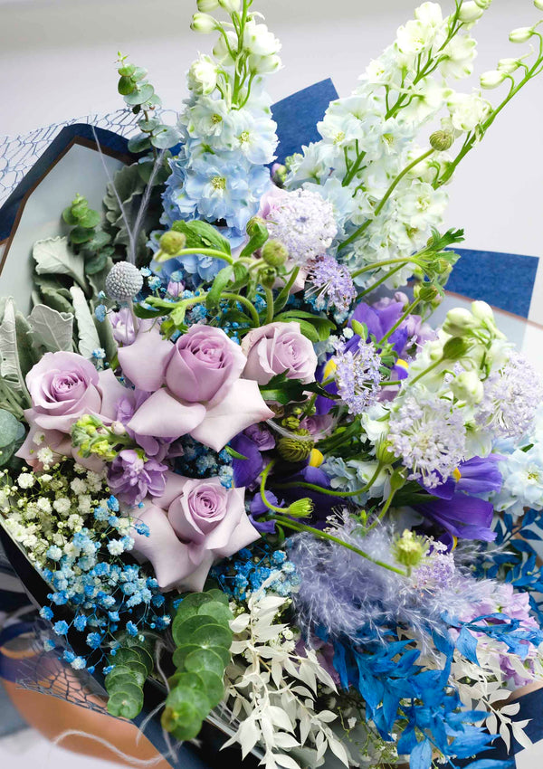 Close up shot of blue theme fresh flower bouquet with lilac roses and sky blue delphiniums designed by top singapore florist floral mikelle specialising in customised flowers
