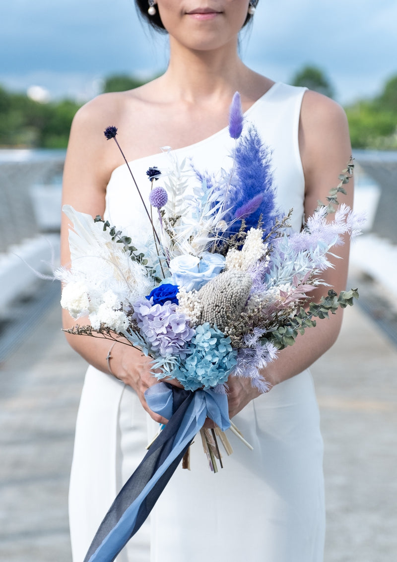 Flowy romantic and new edge bridal bouquet filled of blue preserved roses decorated amongst premium preserved flowers and dried flowers finished in a long silk ribbon