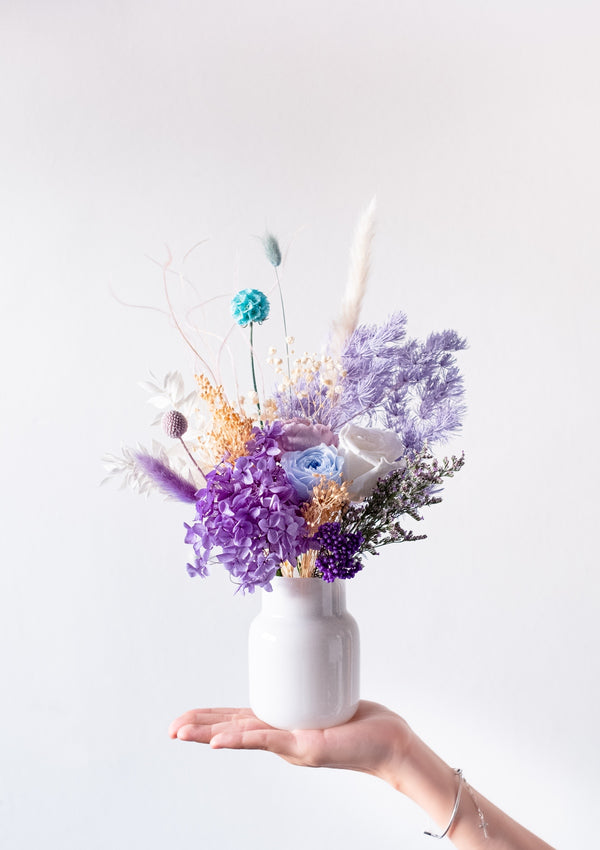 A blue and purple dancing flower arrangement in a vase designed by bespoke florist in singapore floral mikelle