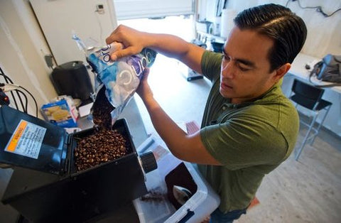 Jason Walsh pouring coffee in coffee grinder.