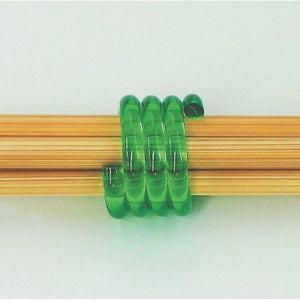 A close up of two knitting needles held together by a Clover Coil Knitting Needle Holder