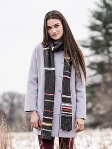 A female model wearing Blue Sky Fibers 21 Color Scarf