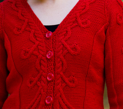 A model wearing a hand-knit cardigan with Celtic cables