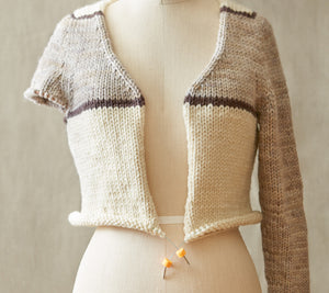 A mannequin wearing a partially knit sweater on a stitch holder that has Cocoknits Stitch Stoppers on the ends