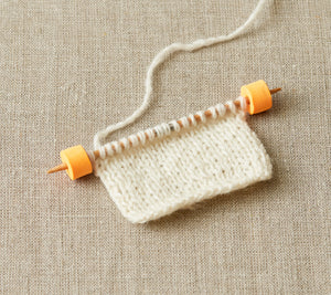 Cocoknits Stitch Stoppers on the ends of a double pointed needle
