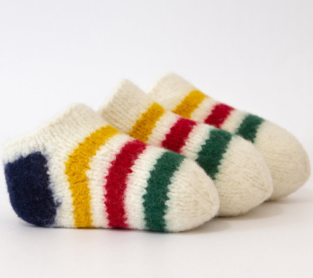 Three RCY Fuzzy Foot Socks in cream with stripes of navy, yellow, red and green