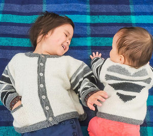 Two children both wearing Love Lines Sweaters in white and grey