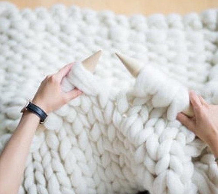 A person knitting a blanket with wool roving in cream colour