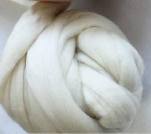 A ball of wool roving in cream colour