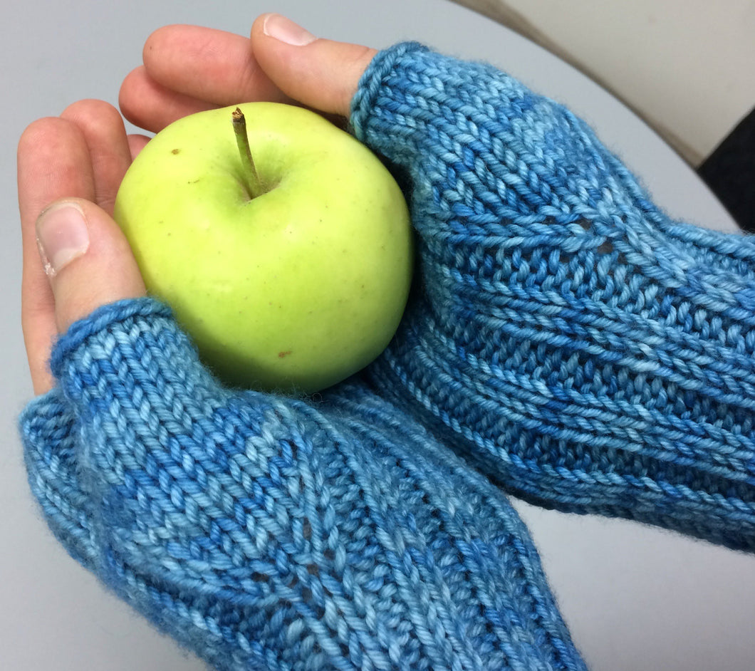 Hands wearing Eve's wristwarmers in RCY Eden colour River and holding an apple