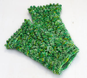 A pair of Queen Vicki's Wristlets knit out of Flash Mob Pages The Wizard of Oz and green mohair