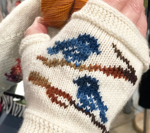 A pair of knitted handwarmers with two birds