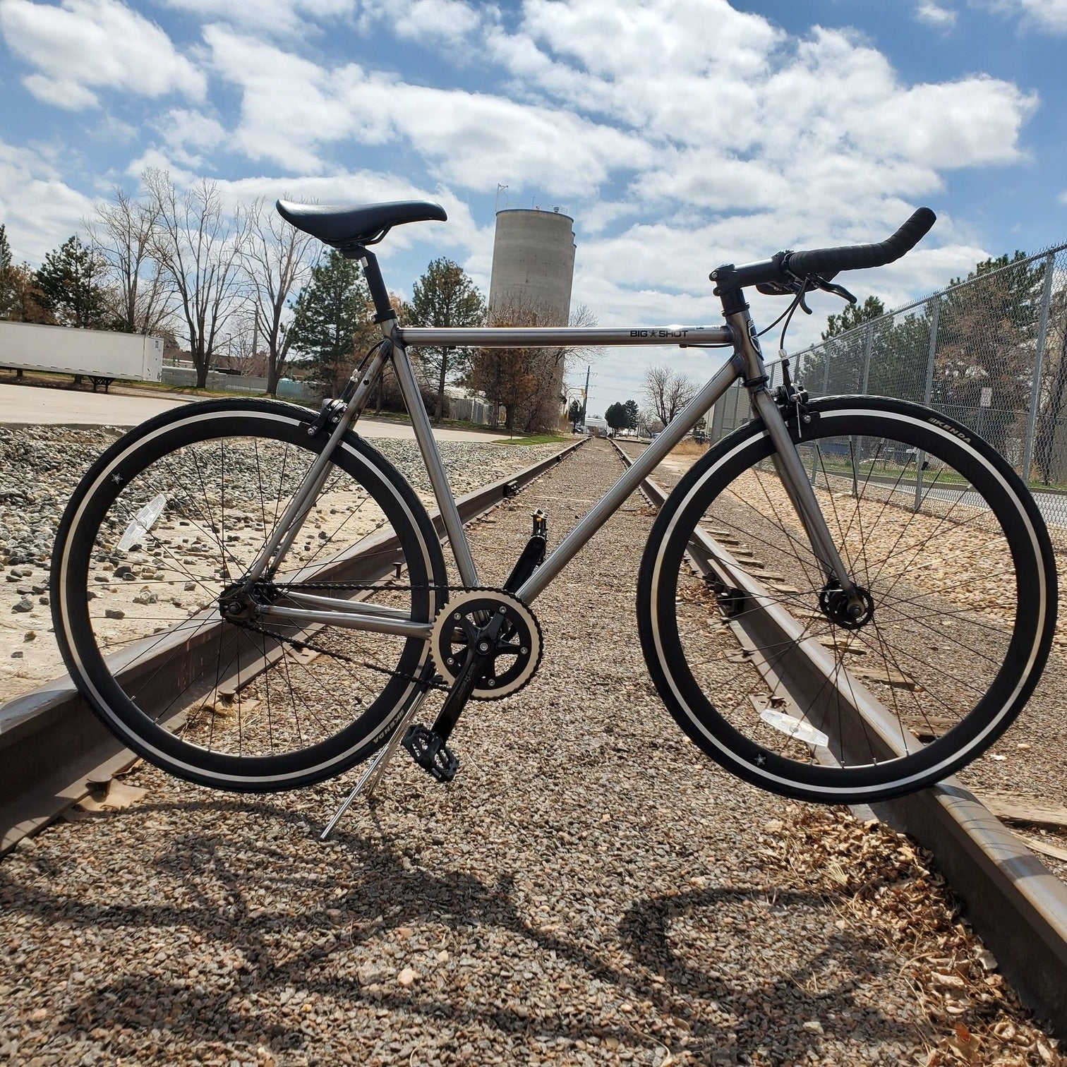 Fixed Gear Bike with a silver frame and black rims on the rail road tracks. Industrial bike.