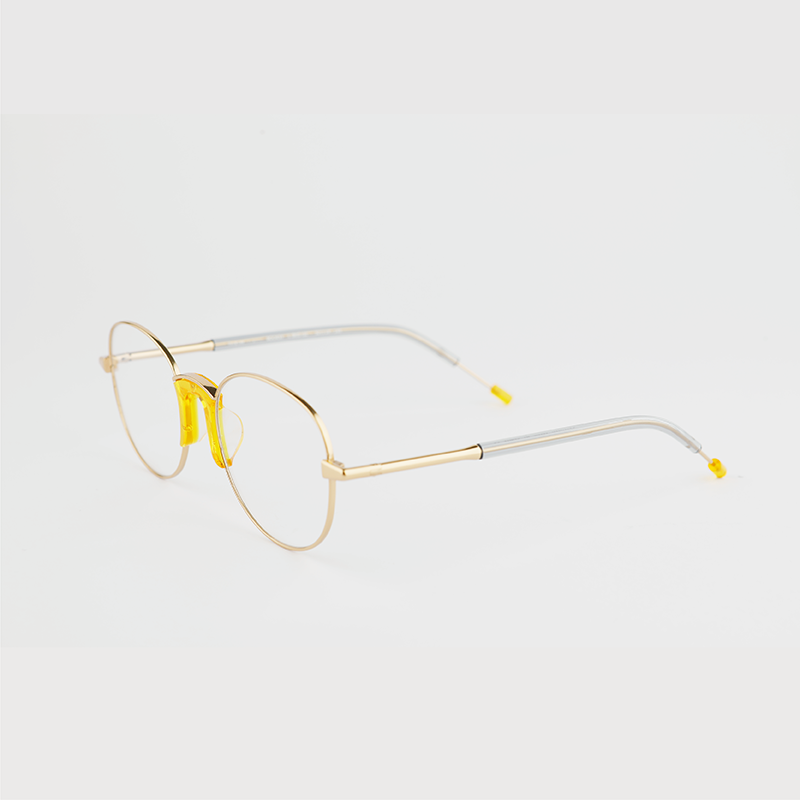 gold colour titanium round optical frame with yellow acetate nose pads and temple tips 45 angled