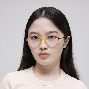 gold colour titanium round optical frame with yellow acetate nose pads and temple tips on model front
