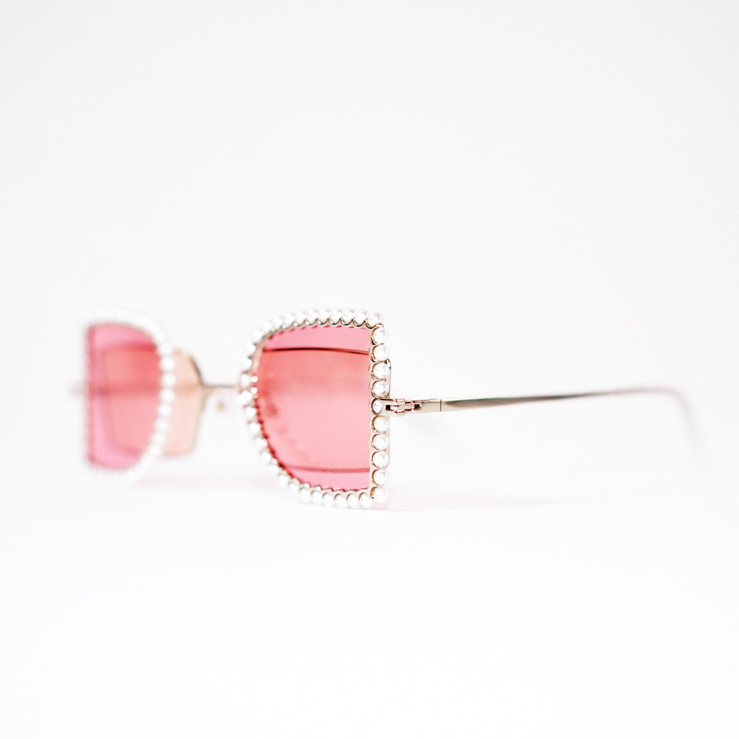sunglasses with pearl rimmed pink windows closed and pink polaroid lens 45 angled 1