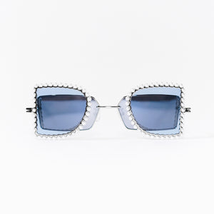 sunglasses with pearl rimmed window closed and blue polaroid lens front
