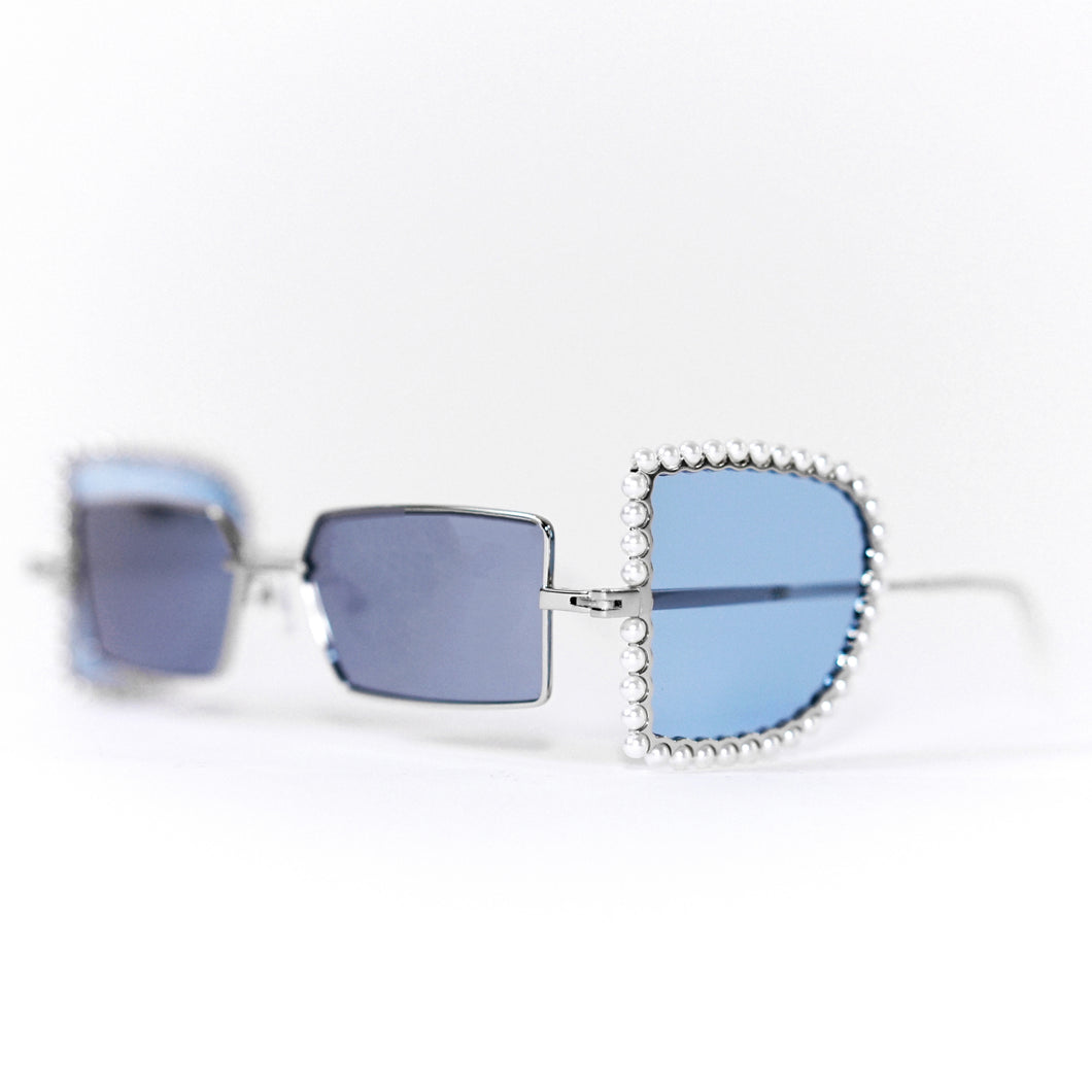 sunglasses with pearl rimmed window opened and blue polaroid lens 45 angled