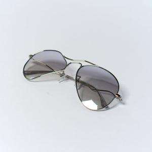 liquified aviator frames in chrome colour with grey polaroid lens temples folded up