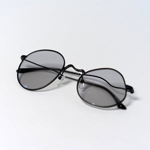 liquified round frames in matte black with grey polaroid lens temples folded up
