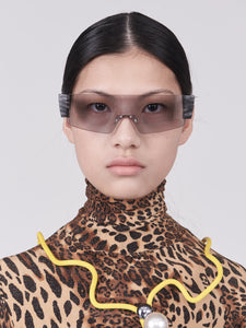 wide safety goggles style sunglasses with grey one-piece lens and marble acetate hinges on model front