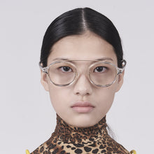 Load image into Gallery viewer, clear acetate round frames with crossed gold rims and clear nylon lens on model front