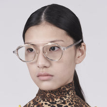 Load image into Gallery viewer, clear acetate round frames with crossed gold rims and clear nylon lens on model 45 angled