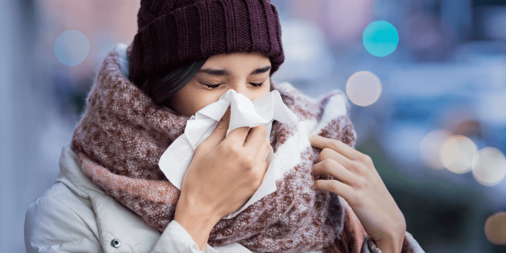 woman blowing nose in the winter cold