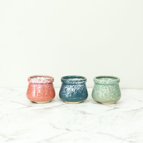 3 glazed pots in a cauldron shape in red blue and green