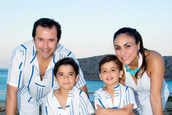 a happy family with white color upf clothing smiling at the beach