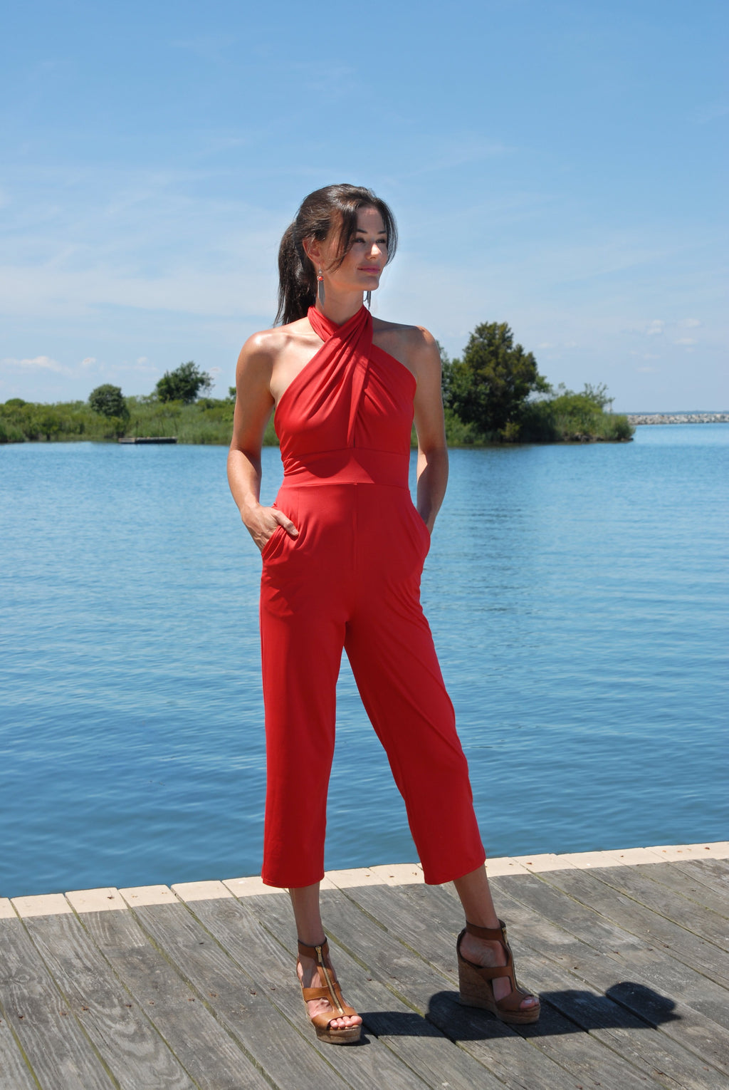 pretty-young-woman-with-brown-hair-standing-next-to-lake-under-the-sun-wearing-red-uv-protective-jumpsuit-designed-for-summer