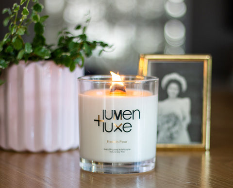 Lumen and Luxe Candle pictured with plant and photo frame