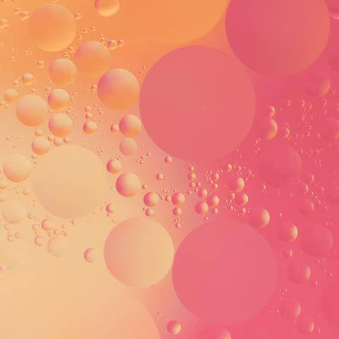 Oil droplets on pink and peach background