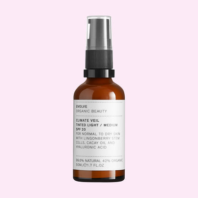 Evolve Climate Veil Tinted SPF20 spray bottle on pink background