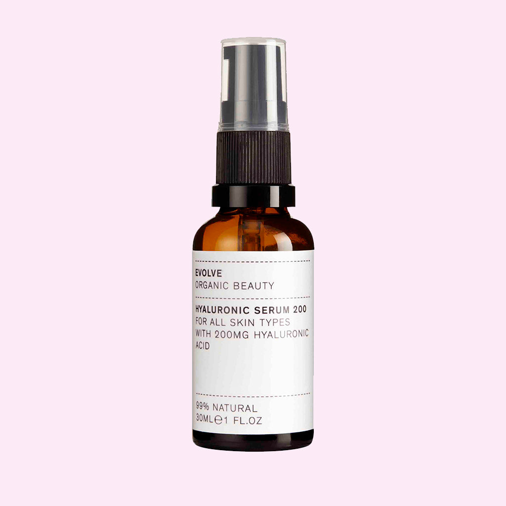Evolve Hyaluronic Serum bottle on pink background