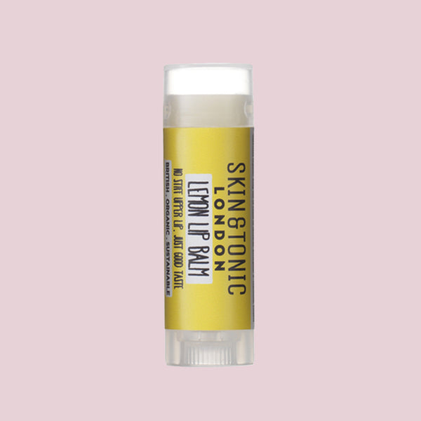 Skin & Tonic Lemon Lip Balm tube on dusky pink background