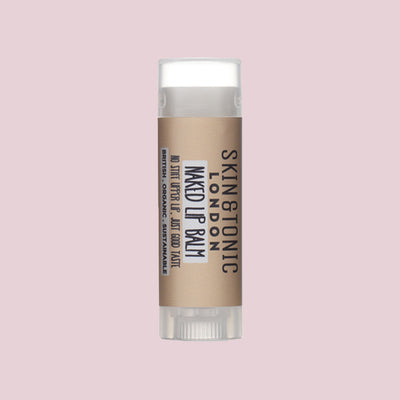 Skin & Tonic Naked Lip Balm tube on dusky pink background