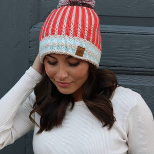 Tangerine striped fleece lined knit hat with pom accent.