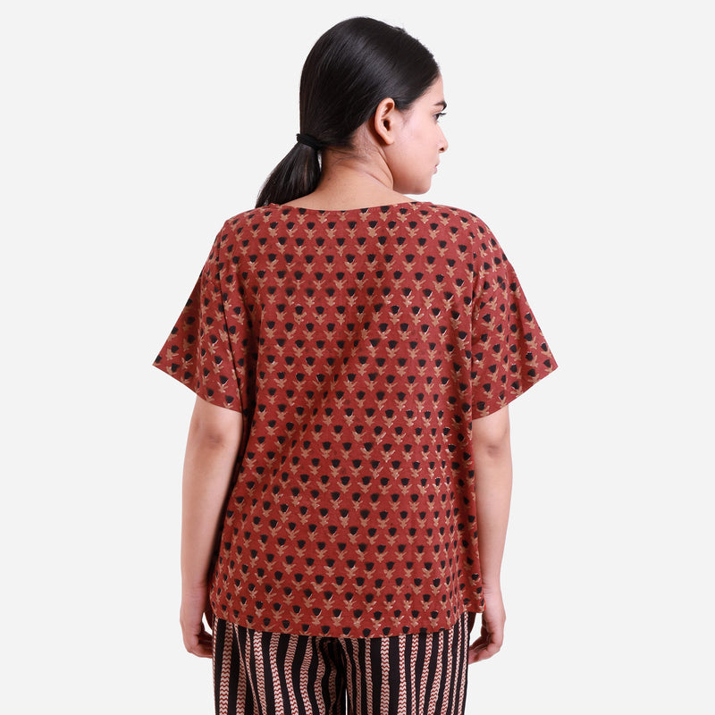 Back View of a Model wearing Brick Red Floral Block Print Straight Top