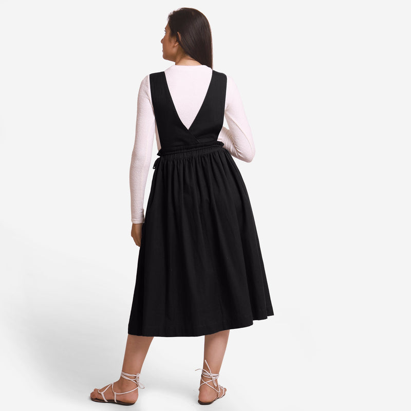Back View of a Model wearing Black Deep Neck Pinafore Midi Wrap Dress