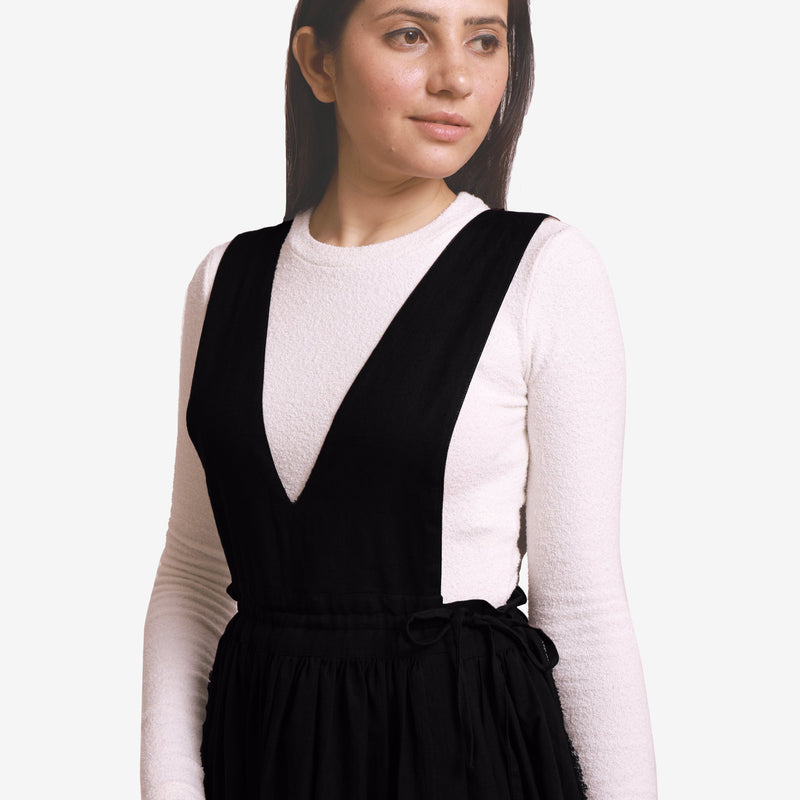 Front Detail of a Model wearing Black Deep Neck Pinafore Midi Wrap Dress