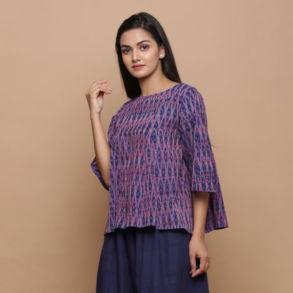 Left View of a Model wearing Blue Ikat Boat Neck Flared Godet Top